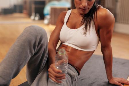 fitness: Tiro colhido da mulher da aptidão segurando garrafa de água no ginásio. Concentre-se em garrafa de água. Mulher sentada na esteira do exercício.