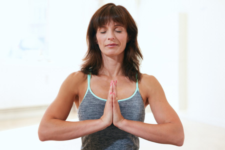 anjali: Portrait of a beautiful mature woman sitting in Anjali Mudra yoga pose at the gym meditating. Female fitness trainer sitting with her hands joined meditating.