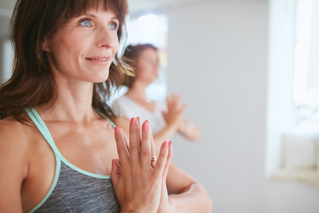 vriksasana: Close up shot of happy mature woman doing yoga looking away smiling. Women in yoga pose vrikshasana using Namaste.