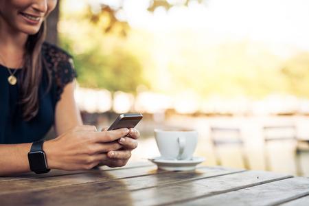 여자는 카페에서 휴대 전화를 사용하여 스마트 워치를 착용. 스마트 폰과 커피와 함께 여성의 손.