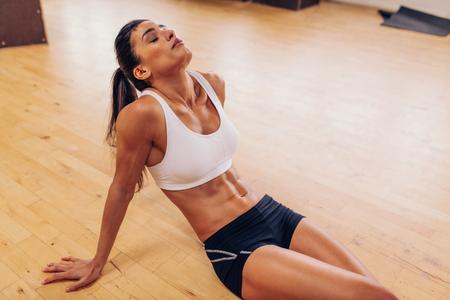 agotado: Retrato de mujer cansada tener descanso despu�s del entrenamiento. Mujer atleta cansado y agotado sentado en el piso en el gimnasio. Foto de archivo