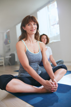 Portrait of female fitness trainer sitting on floor in Baddha konasana yoga pose. Women in yoga class sitting in butterfly pose.