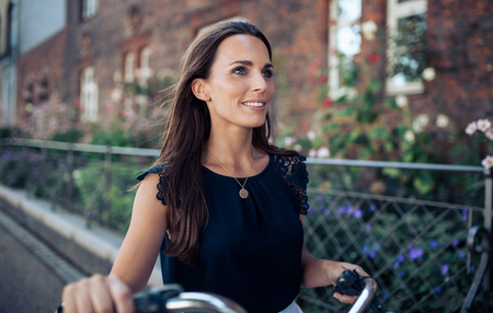 brunette woman: Outdoor shot of happy young woman walking down the street with a cycle looking away. Stock Photo