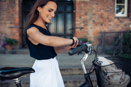 bicyclette: Young woman with a bike checking the time on her wristwatch. Happy woman with bicycle looking at watch, outdoors.