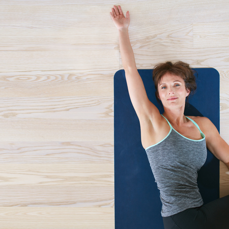 Top view of woman lying and stretching on exercise mat. Female on floor twisting her body and stretching her one hand. Stock Photo