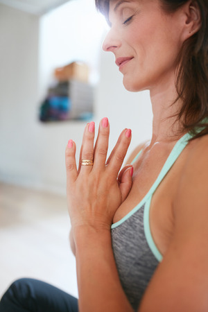 Side view of woman practicing yoga sitting in prayer position. Woman meditating in yoga pose.