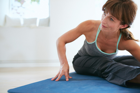 bending forward: Image of woman bending forward doing yoga . Fitness woman practicing yoga on exercise mat at gym looking away.