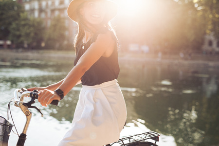 scandinavian people: Portrait of pretty young female riding on her bicycle looking away smiling, with sun flare. Woman cycling on a summer day. Stock Photo