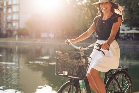 pond: Portrait of attractive young woman riding a bicycle along a pond on a summer day. Caucasian female on bike at park looking at camera.