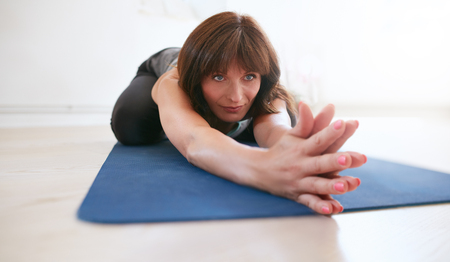 joined: Woman stretching forward with her hands joined looking away. Female fitness trainer performing balasana yoga at gym.