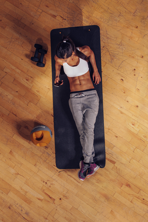 mat: Top view of a young fitness woman relaxing on a yoga mat and using mobile phone. Female reading text message on her smart phone during workout break.