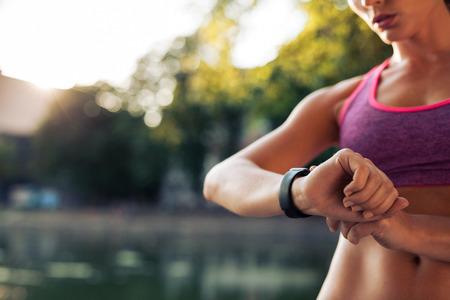 여자는 실행을 위해 피트니스 스마트 시계를 설정. 운동가는 시계 장치를 검사합니다.