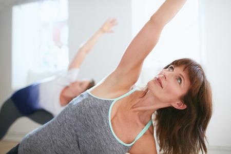 trikonasana: Portrait of mature woman practicing yoga at gym. Fitness female doing Triangle yoga Pose, Trikonasana. Stock Photo