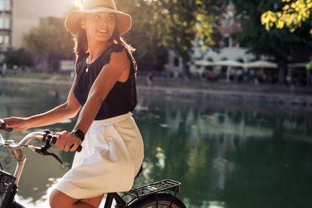 pretty young woman: Portrait of happy young female cycling by a pond looking away smiling. Woman wearing a hat on a summer day riding her bicycle.