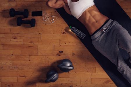 gimnasio mujeres: Vista superior de la joven tumbado en la estera de yoga en el gimnasio. Fitness mujer relajarse después de la sesión de ejercicios con una botella de agua, mancuernas y pesas rusas en el piso.