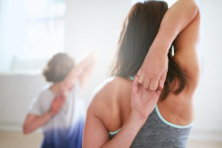 estiramientos: Vista posterior de la mujer en forma haciendo gomukhasana en clase de yoga. Fitness femenino de la mano detrás de la espalda y estiramiento. Tríceps y hombros entrenamiento. Foto de archivo