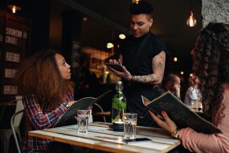 meseros: Retrato de una mujer joven que da una orden a un camarero en un café sentado con su amigo. Camarero poniendo fin a una tableta digital. Foto de archivo
