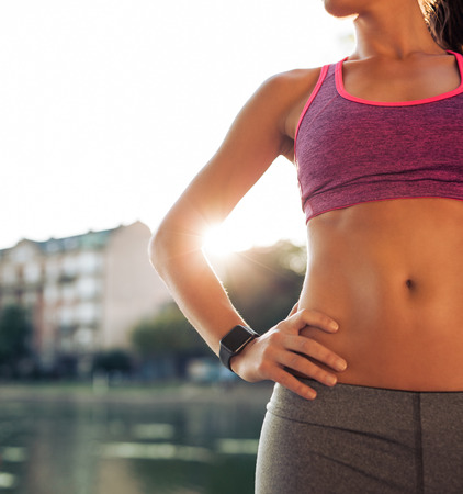 training device: Close up shot of fitness model torso, she is wearing smartwatch standing with her hands on hips. Female athlete relaxing after outdoors workout on a summer day.