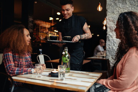 meseros: Remolcar mujeres j�venes sentados en un restaurante, con camarero sirviendo caf�. Amigos femeninos en la cafeter�a.