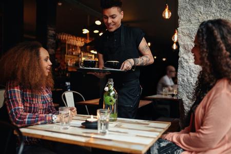 Tow jonge vrouwen zitten in een restaurant, met een ober serveert koffie. Vrouwelijke vrienden op café.