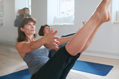 Women practicing stretching and yoga workout exercise together in a health club gym training class session. Two women practicing yoga, bending in boat pose. Performing Navasana in yoga class.