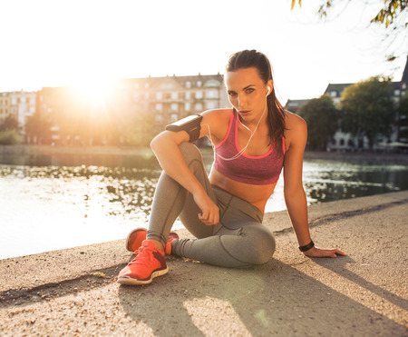 Portrait of fit young woman sitting on the street along a pond. Fitness female taking break from outdoor running training on a summer day.