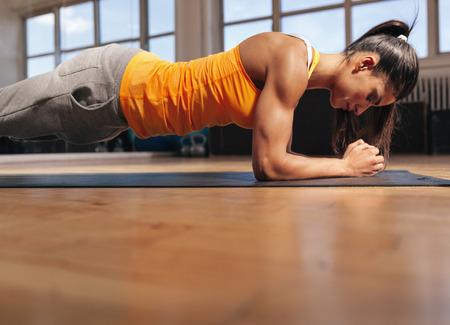 muscular: Mujer joven que hace pilates, trabajando en los m�sculos abdominales. Muscular femenino haciendo entrenamiento de la base en el gimnasio.