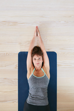 back exercise: Top view of woman lying on floor doing stretching exercise. Fitness woman exercising on yoga mat.