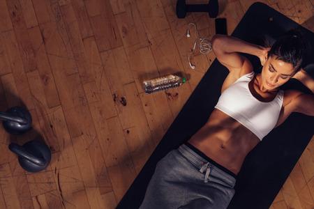 motion: Ovanifrån av kvinnliga gör abs träningspass på gymmet. Muskulös ung kvinna liggande på träningsmatta med händerna bakom huvudet gör magen övningar. Stockfoto