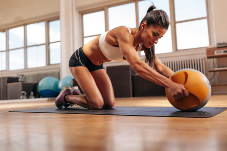 sport training: Strong young woman doing intense workout with kettlebell in gym. Young muscular woman doing core exercise on fitness mat in health club. Stock Photo