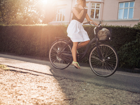 cropped shot: Cropped shot of woman riding bicycle along the street. Female cycling on road with sun flare. Stock Photo