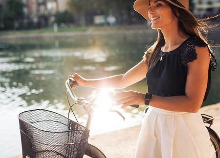 dia soleado: Alegre mujer joven en el parque con su bicicleta. Modelo femenino que lleva el sombrero de la mirada sonriente mientras se camina a lo largo de un estanque.