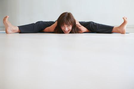 konasana: Smiling woman doing yoga. Wide angle seated forward bend pose. Female practicing  Upavistha Konasana exercise at gym. Stock Photo