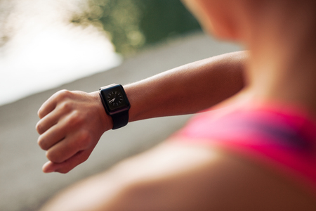 a check: Close up image of young woman checking the time on smartwatch device after jog, outdoors.