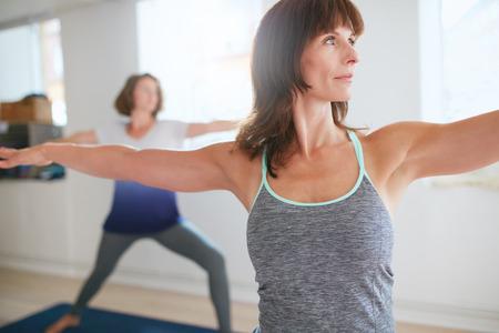 Fitness trainer doet de krijger poseren tijdens de yogales. Yogaleraar uitvoeren Virabhadrasana positie in de sportschool met mensen n achtergrond.
