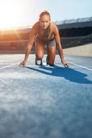 決意を持ってカメラを見上げてスポーツ スタジアムでレース トラックのスタート位置に若い女性スプリンター。競馬場スターティング ブロックの 写真素材