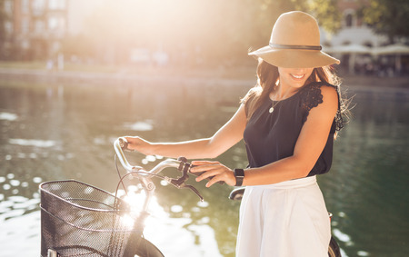 summer dress: Attractive young woman wearing hat at the park with her bicycle. Beautiful female model looking down smiling. Stock Photo