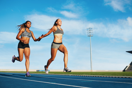 athletics track: Young woman running a relay race and giving relay baton to her teammate. Female runner passing the relay baton during race. Stock Photo