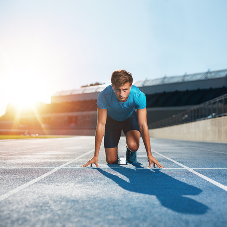 Fit and confident man in starting position ready for running. Male athlete about to start a sprint looking at camera with bright sunlight.