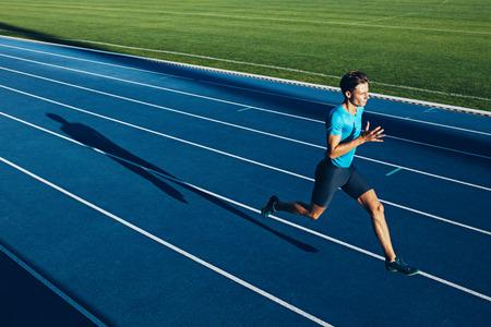 correr: Disparo de una joven formación atleta masculino en una pista de carreras. Sprinter corriendo en pistas de atletismo.