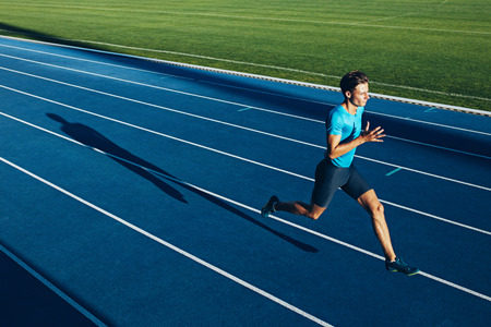 Shot van een jonge mannelijke atleet training op een circuit. Sprinter draait op atletiekbanen. Stockfoto