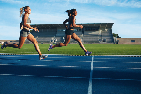 Athletes arrives at finish line on racetrack during training session. Young females competing in a track event. Running race practicing in athletics stadium.
