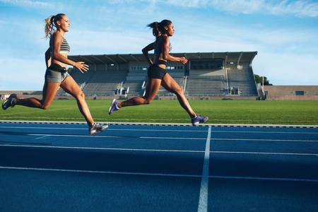 Atletas llega a línea de meta en la pista de carreras durante la sesión de entrenamiento. Las mujeres jóvenes que compiten en un evento de pista. Correr la carrera que practica en estadio de atletismo.