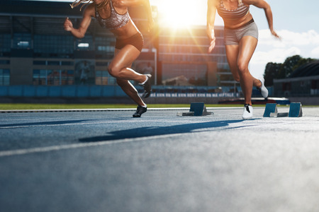 athletic: Sprinters starts out of the blocks on athletics racetrack with bright sunlight. Low section shot of female athletes starting a race in stadium with sunflare. Stock Photo