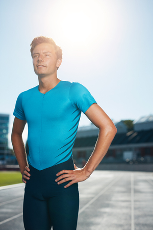 off track: Professional man athlete standing with his hands on hips looking off camera into the distance. Sprinter stands in lane at the athletics track in a outdoor athletics stadium.
