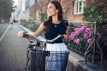 walking down: Cheerful young woman looking away while walking down the street with a bike. Female with a bicycle on city road looking at a view smiling. Stock Photo