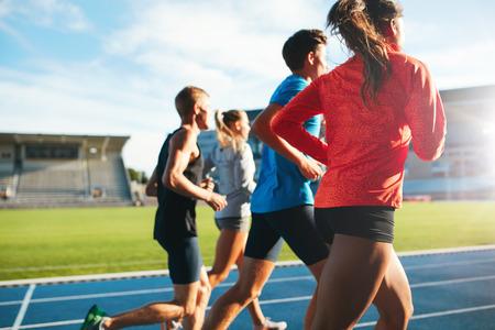 Vista posterior de los jóvenes que se ejecutan juntos en pista de carreras. Los atletas jóvenes que practican una carrera en la pista de atletismo del estadio. Foto de archivo