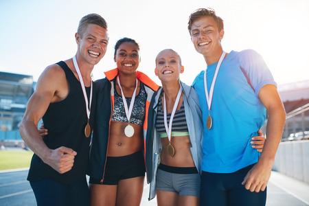 atletismo: Atletas multirraciales felices celebrando la victoria, mientras que de pie juntos en pista. Grupo de corredor con medallas ganadoras de un concurso.