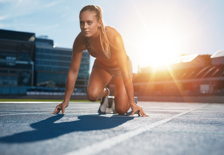 athletics track: Fit and confident woman in starting position ready for running. Female athlete about to start a sprint looking away. Bright sunlight from behind.