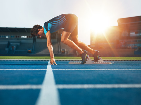atletismo: Atleta de sexo masculino en posición en atletismo pista de partida. Corredor practicar su carrera de sprint en pista de carreras de atletismo del estadio. Foto de archivo